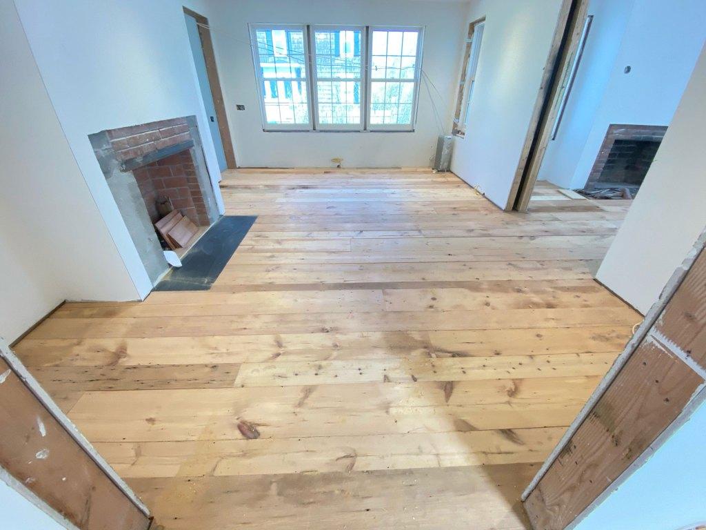 pumpkin pine flooring installation near fireplace