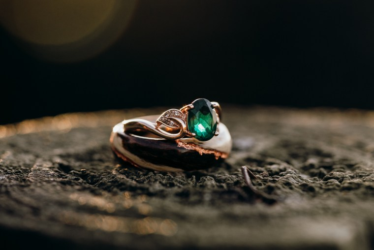 A rose gold and emerald engagement ring sits perfectly within a larger dark wood ring. The two - offered as dual wedding proposal rings and are now shown sitting atop a rustic looking fence post.