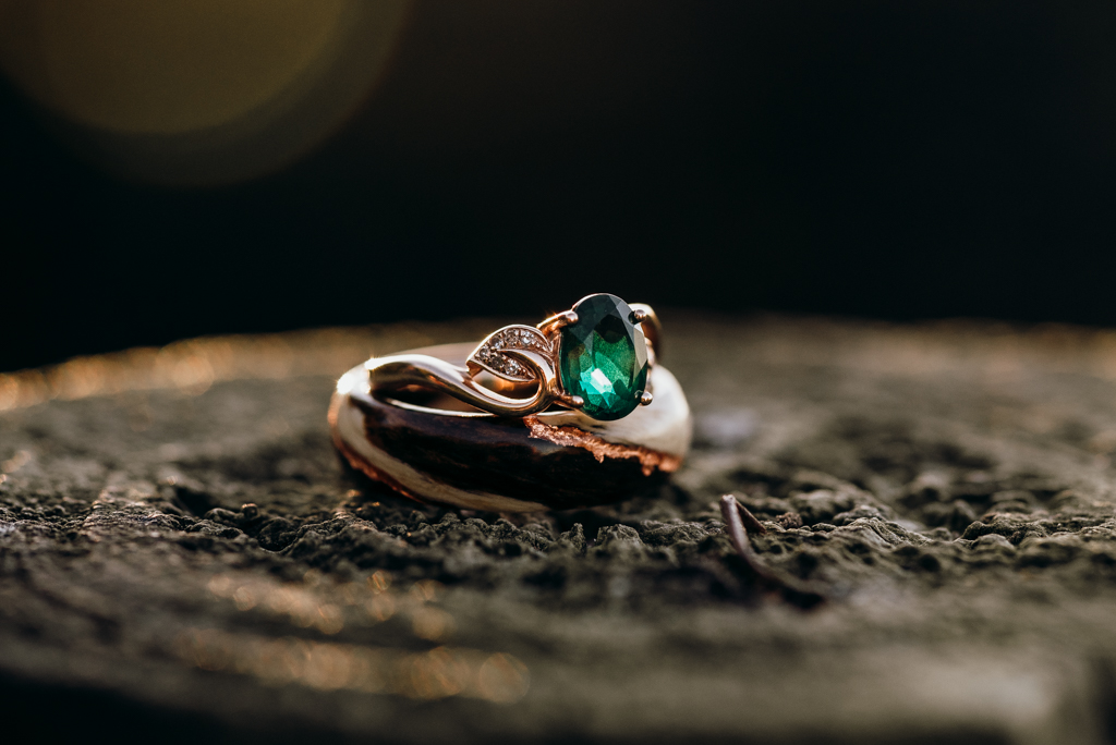 Two wooden, rose gold and emerald engagement rings stacked on a fence post.