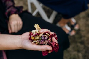 A hand grasps a bunch of handmade leaf confetti - brightly coloured and full of rose petals, leaves and herbs.