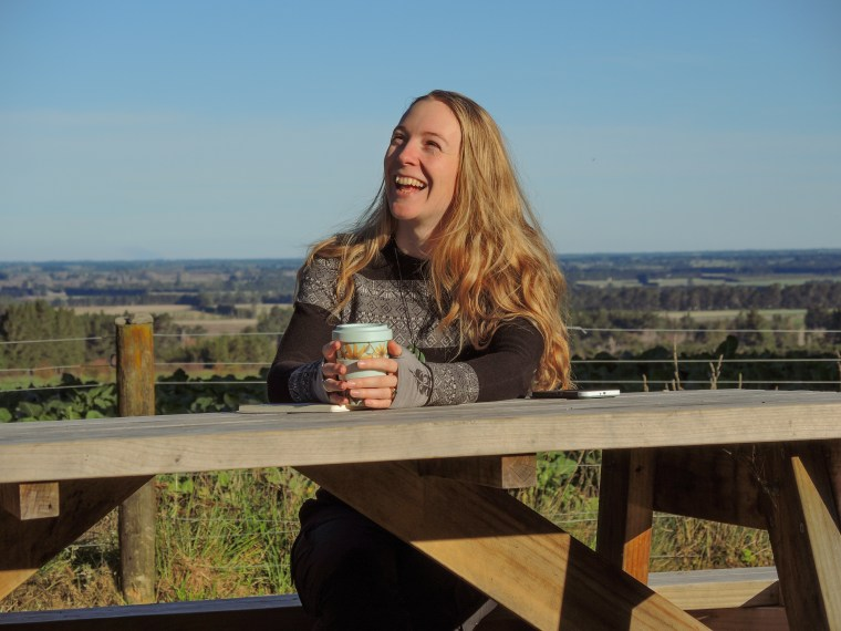 Jodie Munro, eco-friendly wedding planner and owner of Emerald and Ebony sits at a picnic table laughing, keep cup in hand.