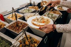A bride chooses her food from a selection of wedding buffet food.