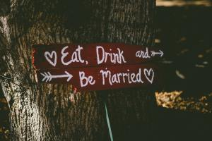"""A wooden sign nailed to a tree reads, """"Eat, Drink and Be Married"""""""