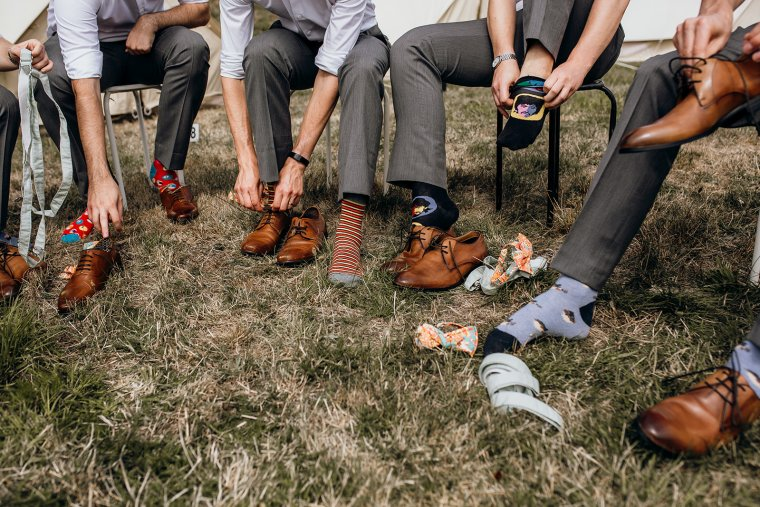 A group of groomsmen pull brown leather shoes over their novelty socks