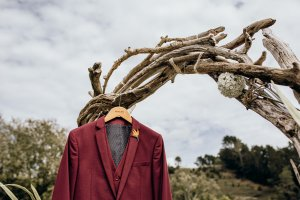 A burgundy wedding suit hangs from a driftwood arch
