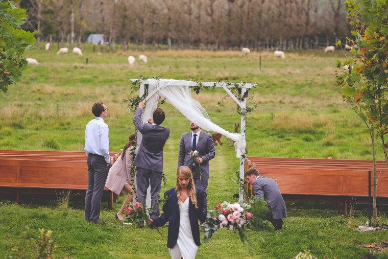 A wedding crew work together to pull down the wedding arch after the ceremony.