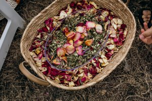 A cane basket sits on the ground full of sustainably dried rose petals and hole punched leaves ready to be thrown as eco-friendly wedding confetti.