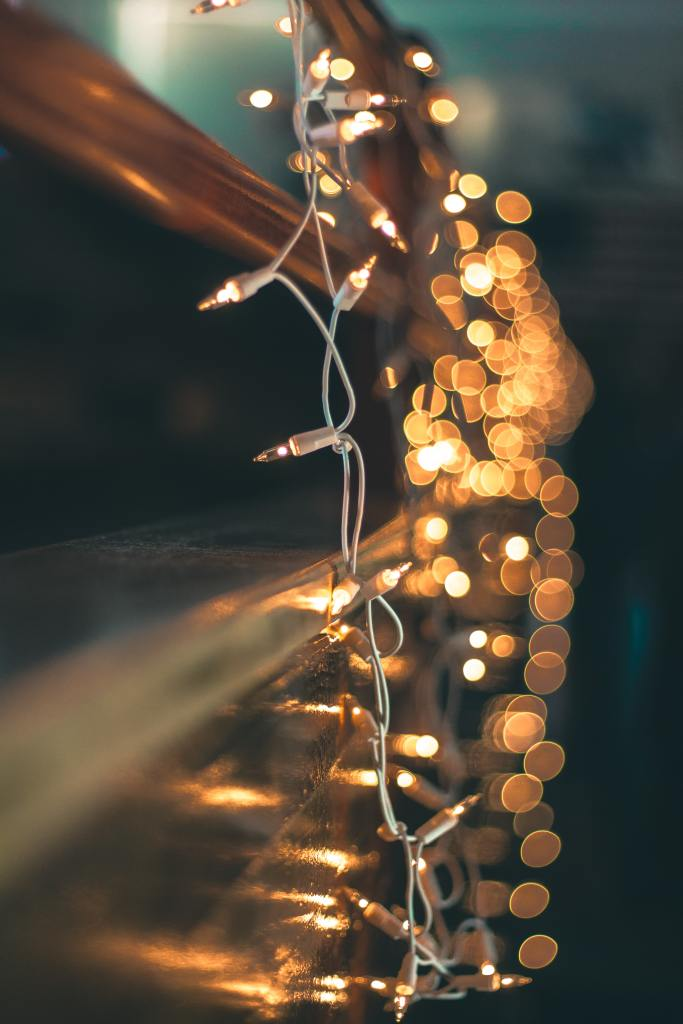 An artistic shot of a fairy light string hanging in a window - the reflections dancing on the glass