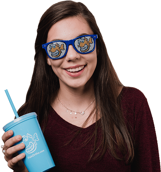 young girl smiling, straight white teeth, fishbein orthodontics logo on blue sunglasses, holding blue cup with fishbein othodontics logo