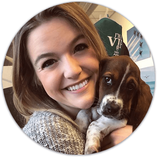 Young woman Fishbein Orthodontics, holding brown puppy in arms