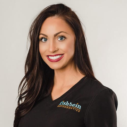 Fishbein Orthodontics Team member brittany, smiling straight white teeth, long brown hair, black v-neck