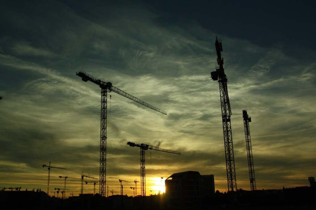 Cranes over a building site at sunset