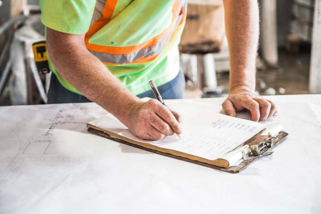 Construction worker wearing safety reflective clothing, writing on clipboard