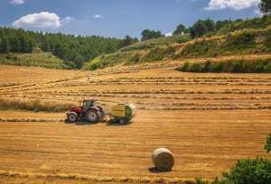 A tractor in a field baling hay - safety on the farm