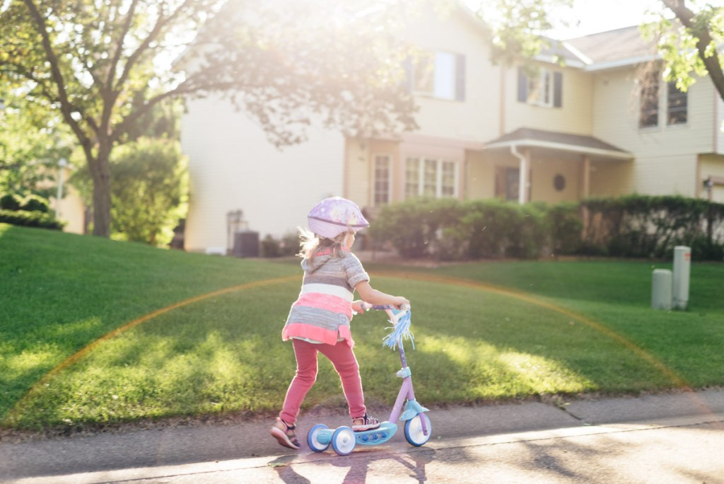 Girl riding scooter through neighborhood