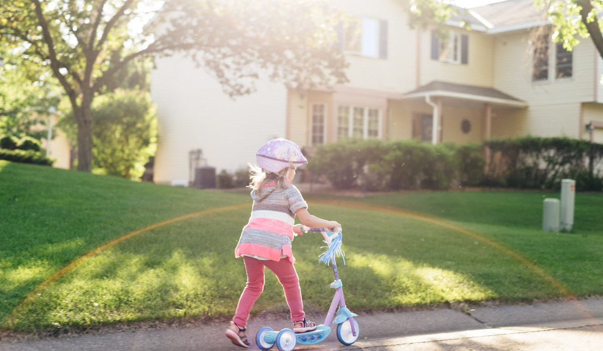 Girl riding scooter through neighborhood