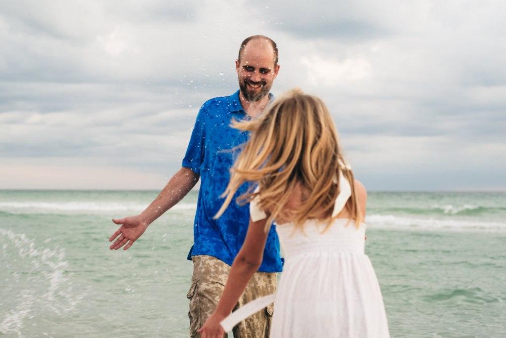 Daughter splashing dad in the ocean