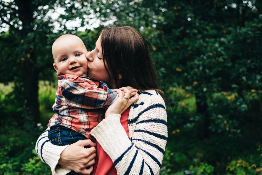 Mother kissing son's cheek documentary photo.