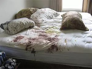 room in need of crime scene cleaning blood on mattress and linens