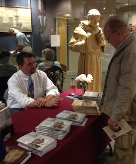 I teach at a Franciscan university, so it was only appropriate that St. Francis (background) keep me company as I signed books at VMI.