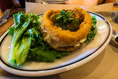 Green chile cheeseburger (made with a chicken breast) and topped with salsa, cheese and an onion ring at Burger Jones