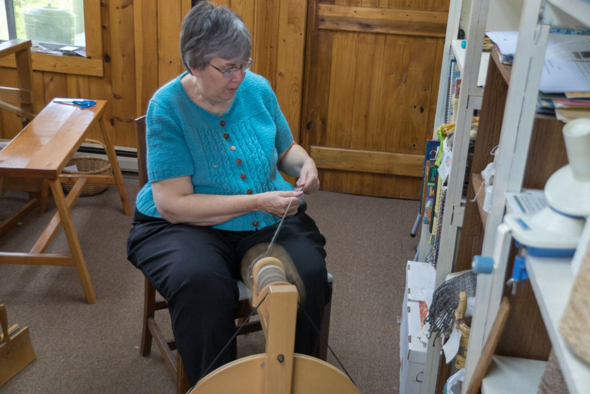 A weaver demonstrates spinning yarn at the Foxfire Museum and Heritage Center