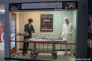 Movie prop with alien on exam table being observed by a doctor and a man in a suit and hat