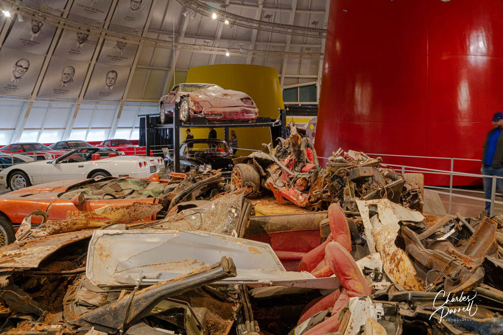 National Corvette Museum sinkhole display in large room showing six demolished Corvettes and restored Corvettes in the background