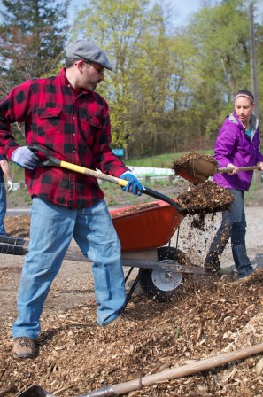 Bryce and Alicia fill a wheelbarrow with mulch.
