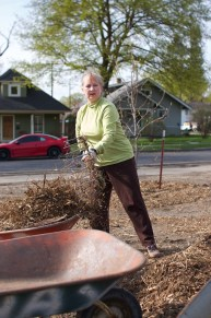 Melissa scoops mulch into the wheelbarrow.