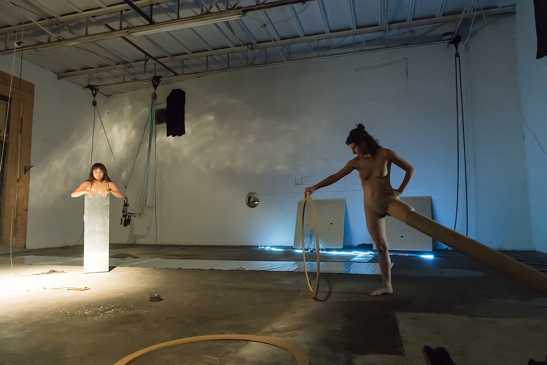 Person holding a plastic mirror and another person with their leg inserted in a long cardboard tube and holding a wooden hoop