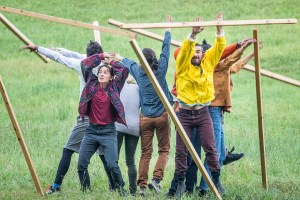 A group of people in the middle of wooden pillars falling down, in a grass field