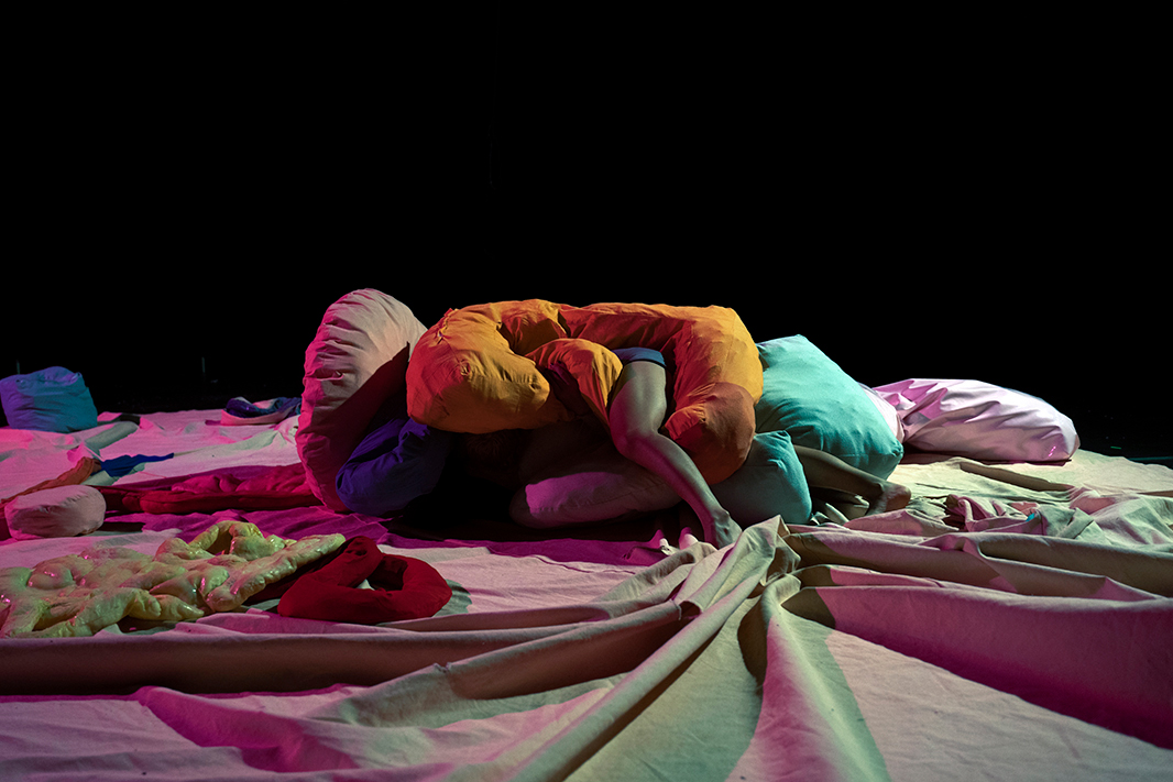 Dancer hiding in the middle of a big pill of unusual soft and colorful cushions