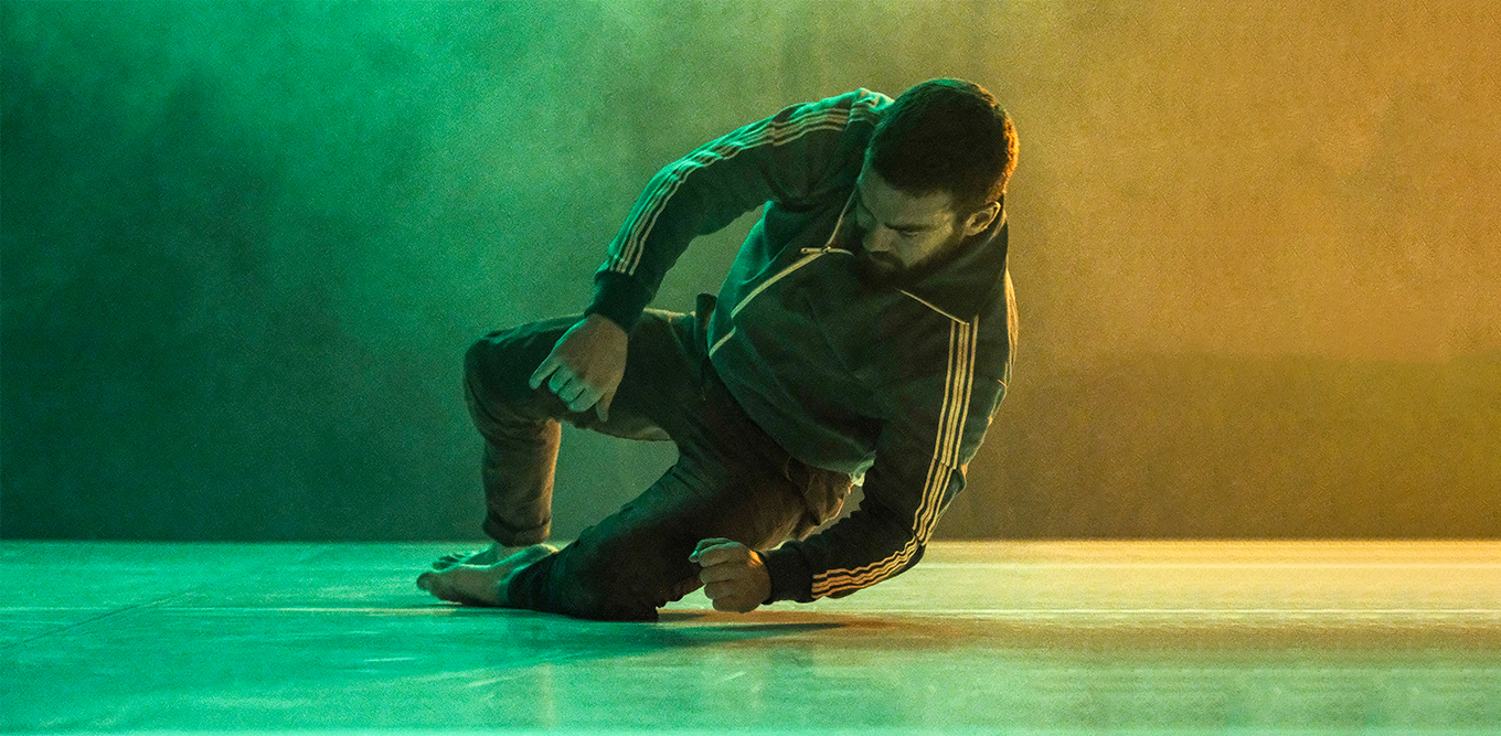 Emile falling down on the floor in a green and yellow lighting