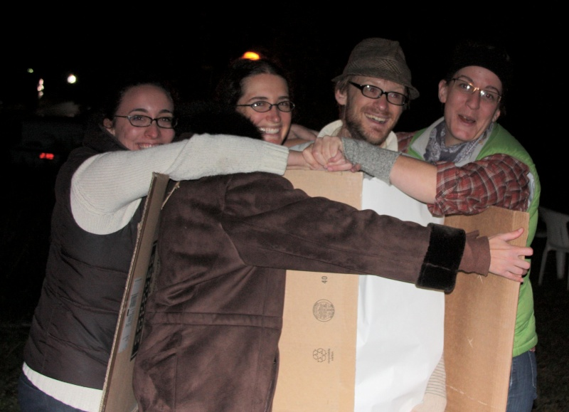 four people hugging in a row, wearing a cardboard square, a chocolate brown coat, a white paper tube, and a cardboard square