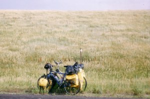 two bikes leaning on a post by the road with grasslands behind them
