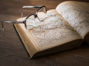glasses on book with maps inside