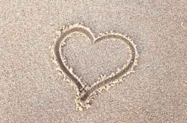 a heart drawn in beach sand
