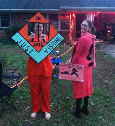 """Jessica in orange scrubs holding an """"in jail, just visiting"""" sign with bars over her face, and Emily in orange with a question mark on her back holding a large Chance card"""