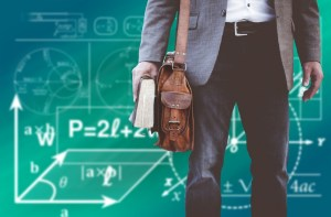 man holding book with bag on his shoulder, in front of chalkboard with math equations