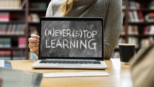 """laptop on desk in library; the screen looks like a chalkboard and says """"never stop learning"""""""