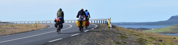 three people on bicycles with bags, biking along the coast