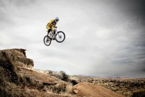person on dirt bike jumping off small cliff