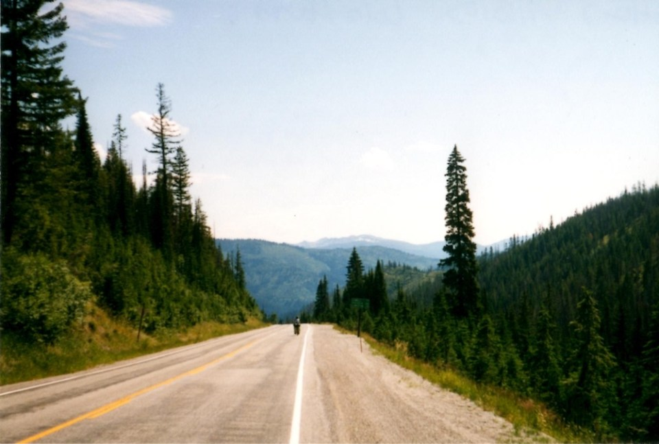 a view down Lolo Pass with a road and a bicyclist in the distance, mountains beyond, and evergreen trees lining the road