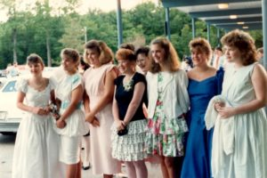 eight teenage girls in formal dresses outside a school, posing for a photo