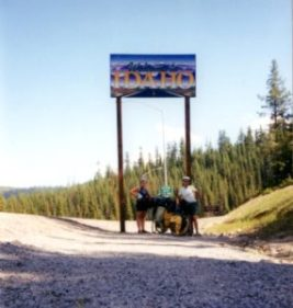 """two women with loaded bicycles under a tall sign that says """"Welcome to Idaho"""" with evergreen trees in back"""
