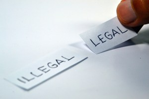 words illegal and legal on slips of paper, fingers are choosing legal