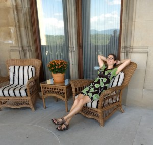 person in dress leaning back in wicker chair with cushions, outdoors on stone patio