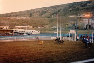 cowboys chasing calf across arena during calf roping event, mountains in background
