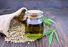 hemp-oil-in-glass-bottle-next-to-hemp-seeds-and-leaves-on-wooden-table